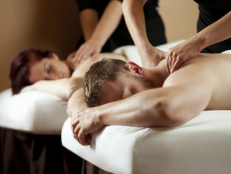 Couple lying on separate tables getting mobile massage