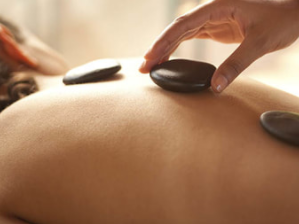 mobile massage therapist putting hot stones on the back of clients as she gives a hot stone massage