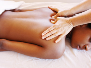 woman lying on a table getting a swedish massage from therapist